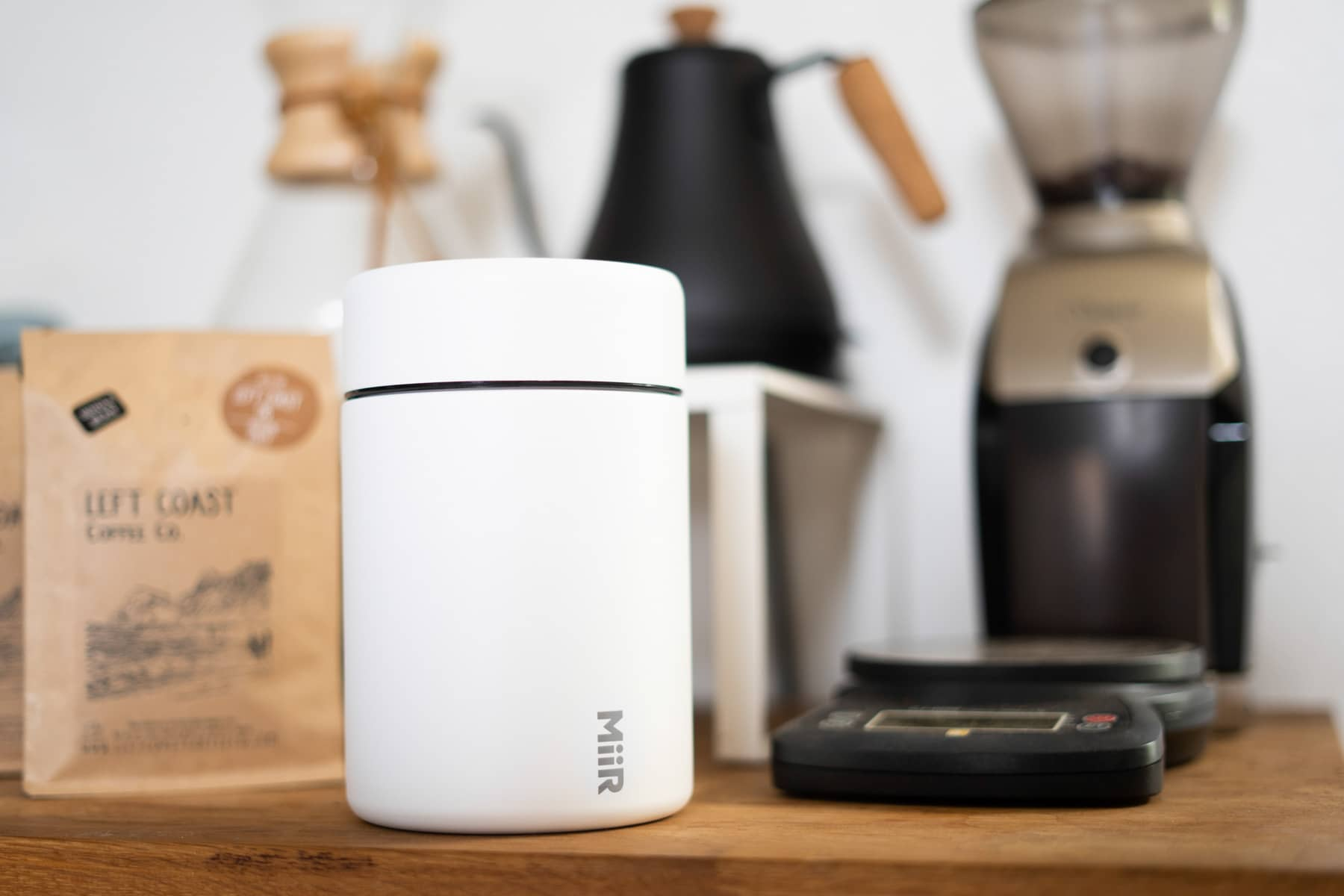 Closed white coffee canister in front of a coffee maker and a bag of coffee