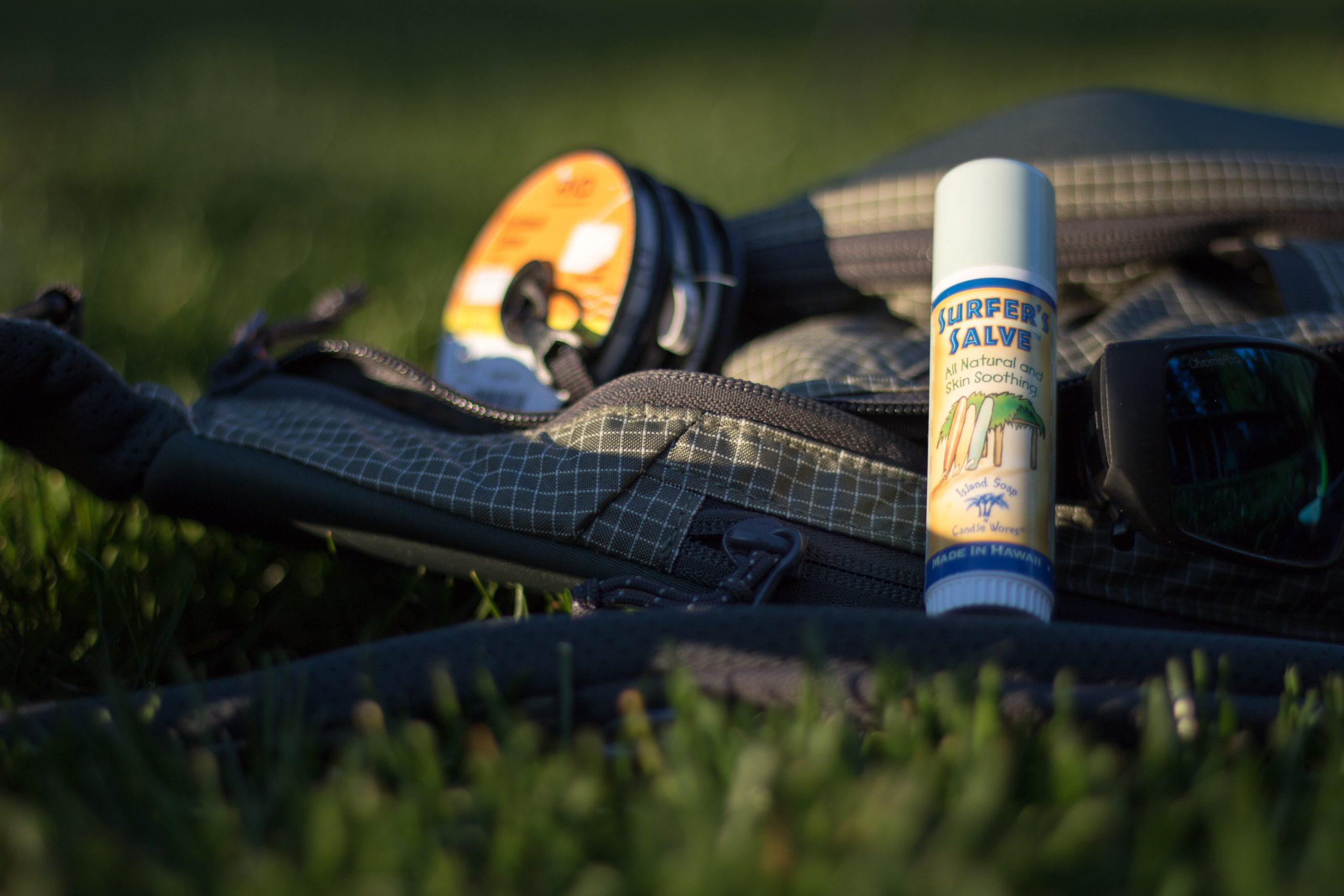 A stick of Surfer's Salve sitting against sunglasses and fly fishing gear