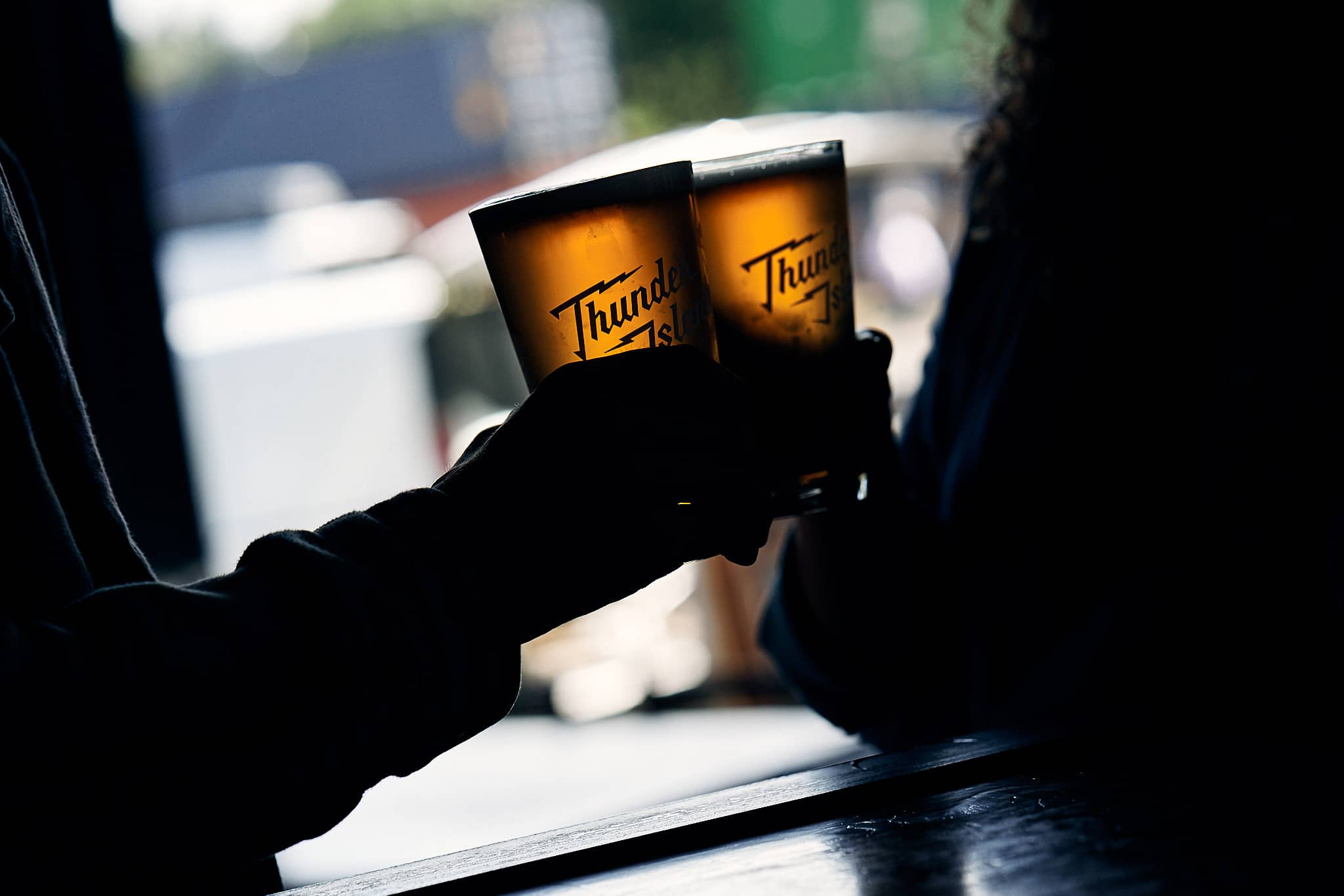 Cheers with two Thunder Island Brewing branded pint glasses