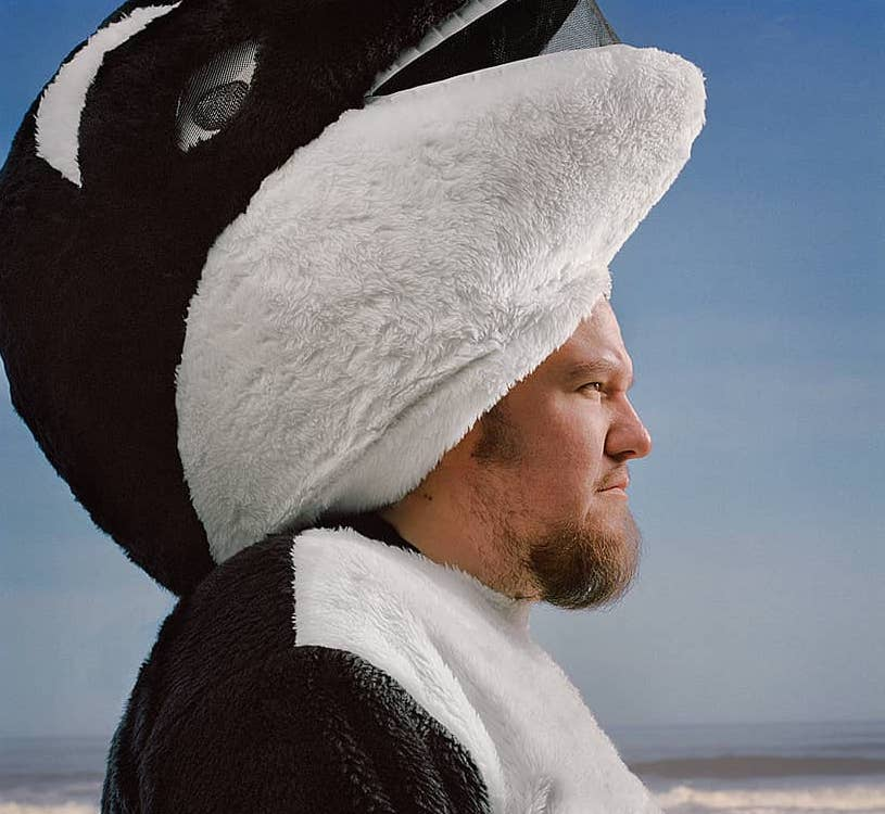 Erik Urdahl from The Spout standing on a beach in a killer whale costume