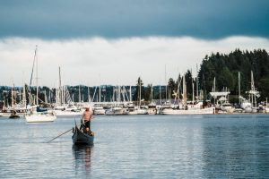 A gondola in Gig Harbor rowing away from docks full of yachts and sailboats.