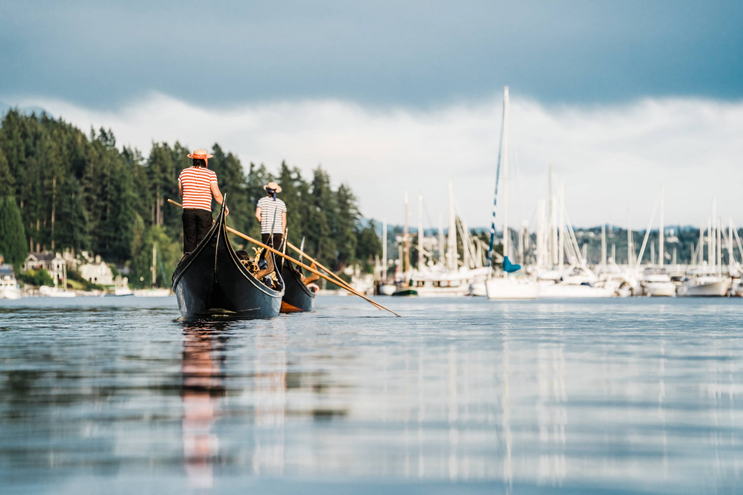 The Gig Harbor Gondola boats rowing in tandem towards sailboats.