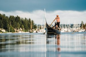 A gondola rowing through Gig Harbor with a dark sky in the background