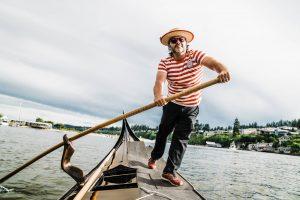 Gig Harbor Gondola owner John Synco rowing on the back of a gondola