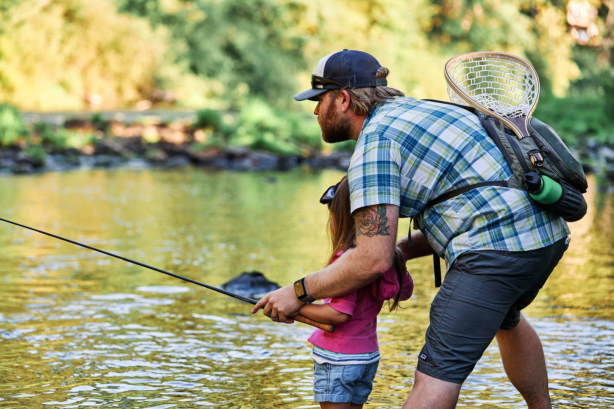 Dad watching the water while teaching his daughter to fish