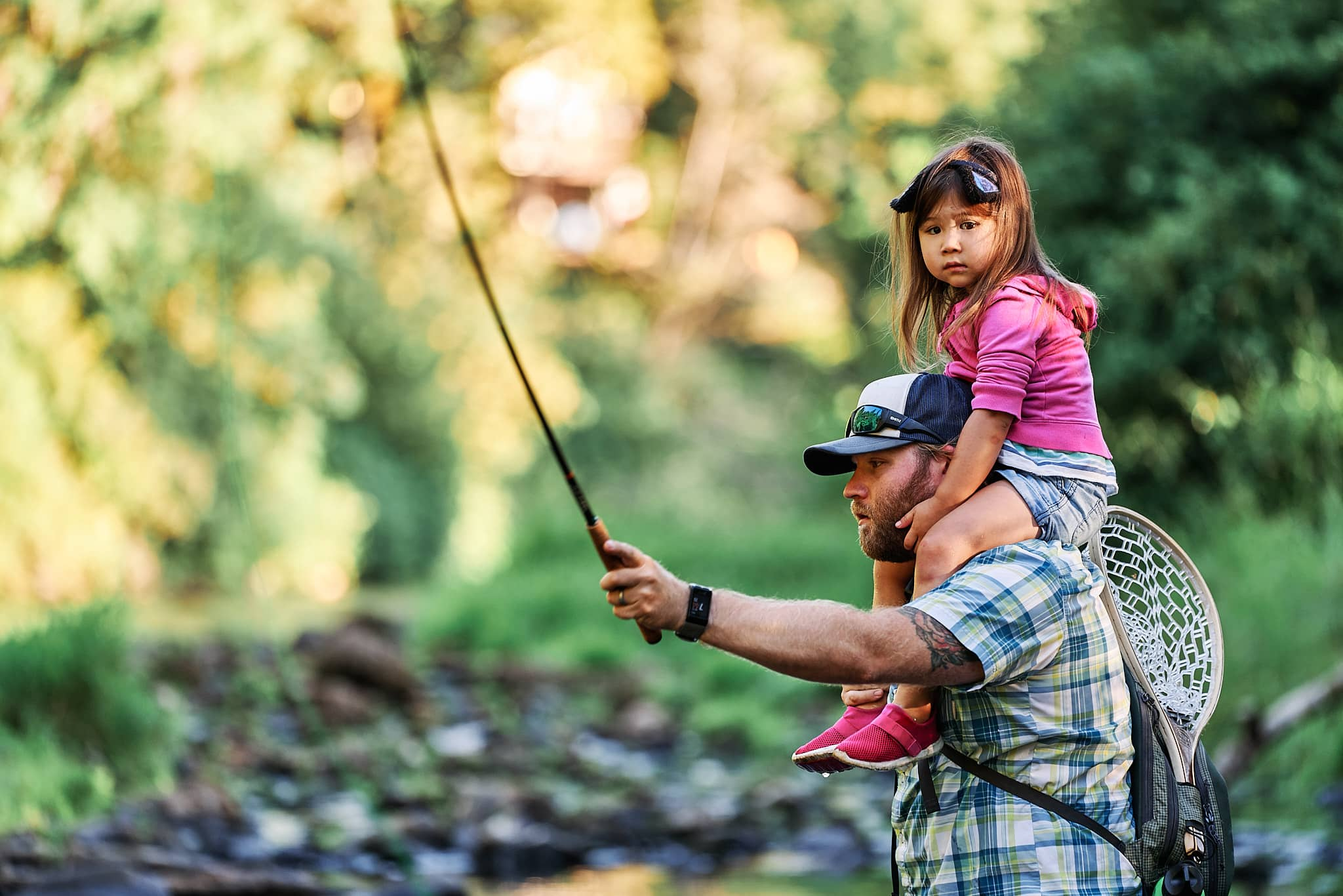 Man casting a fishing rod while his daughter sits on his shoulders