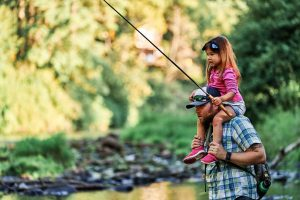 McKenzie holding a Tenkara rod in a river on Dad's shoulders