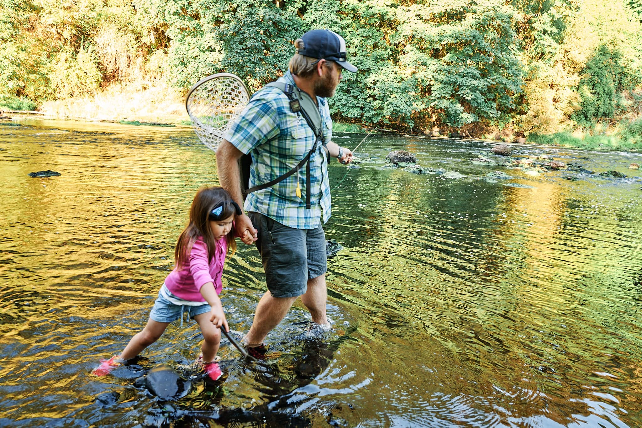 McKenzie and her Dad walking through a shallow river while casting a Tenkara rod