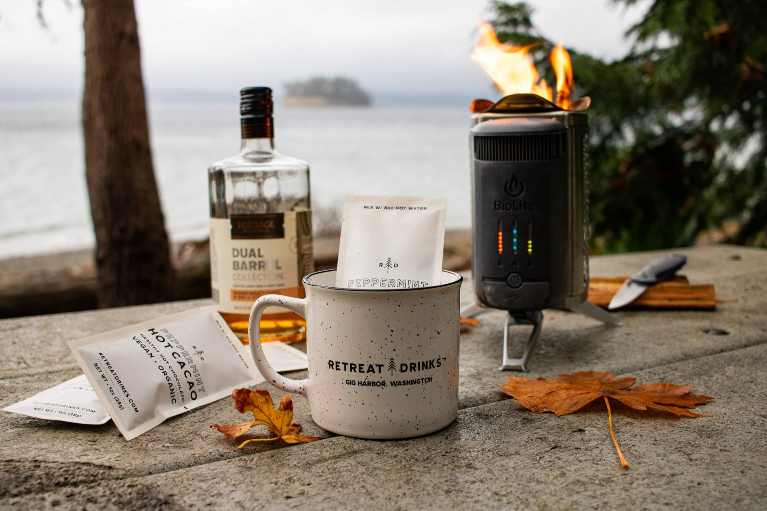 A Retreat Drinks mug with packs of peppermint on table on the shores of Puget Sound