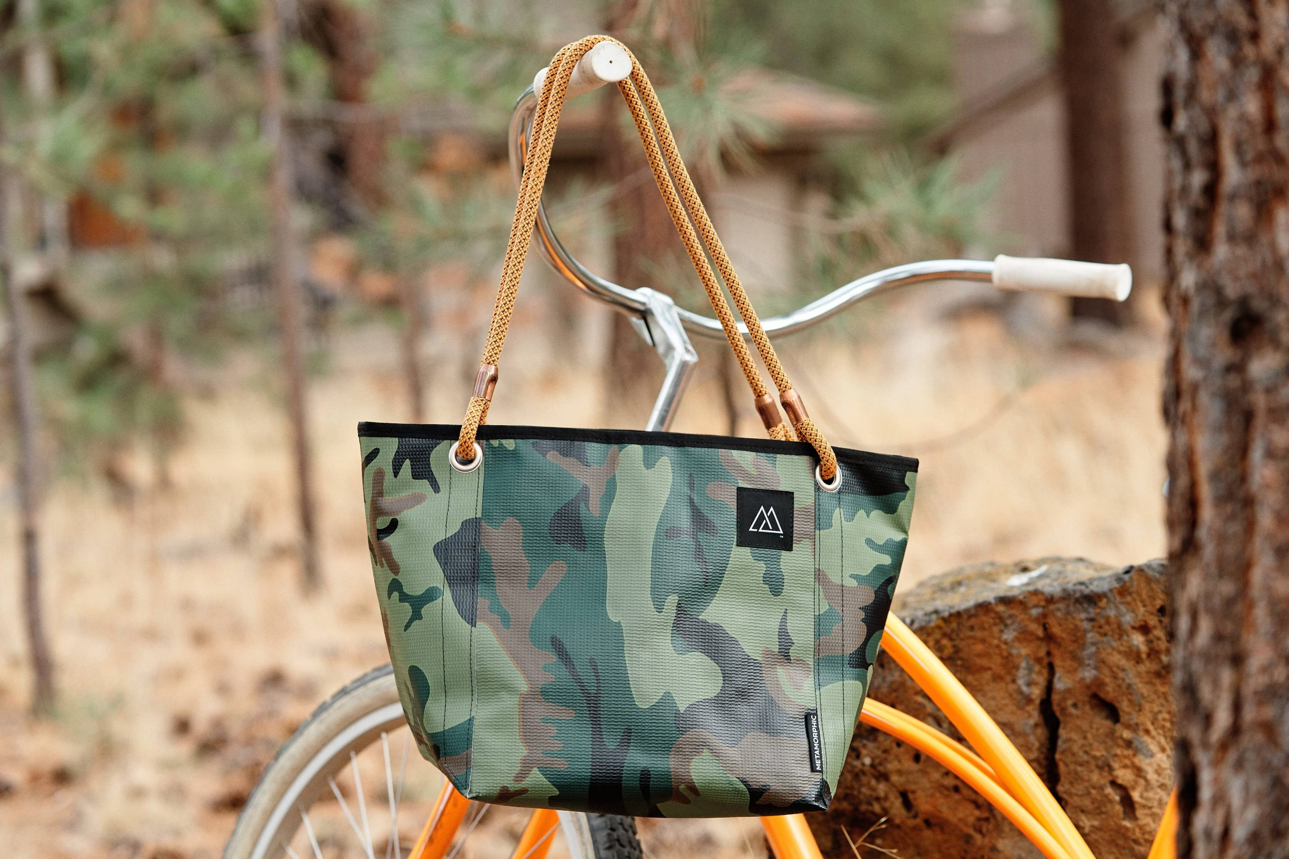 Metamorphic Gear's Deluxe Tote hanging on the handlebars of an orange bike